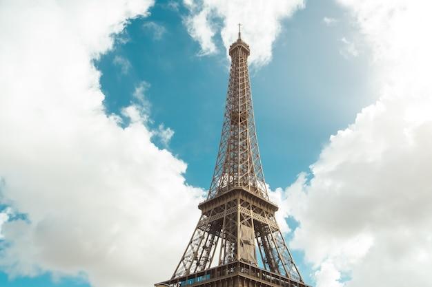 Amore a parigi. la torre eiffel e la forma del cuore nelle nuvole - concetto di san valentino o viaggio romantico