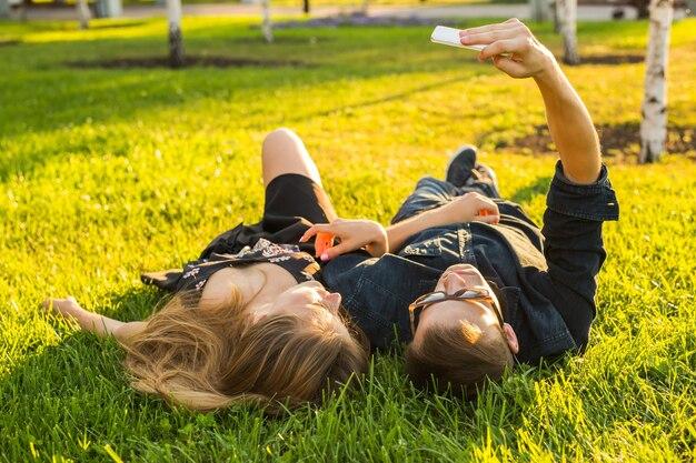 Concetto di amore e persone. felice coppia adolescente sdraiato sull'erba e prendendo selfie sullo smartphone in estate.