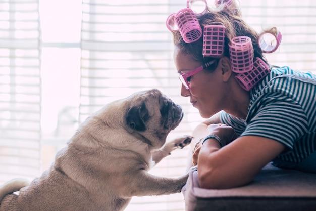 Amore e concetto di pet therapy con donna scena domestica e cane migliore amico che si baciano e guardano - carlino romantico e situazione femminile - vita con animali durante il blocco