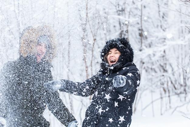 Concetto di amore, relazione, stagione e amicizia - uomo e donna che si divertono e giocano con la neve nella foresta invernale