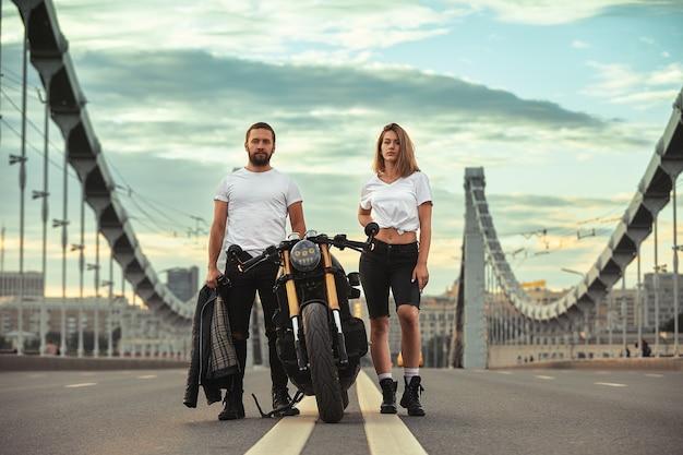Amore e concetto romantico bella coppia in moto si trova uno di fronte all'altro in mezzo alla strada sul ponte, su doppio solido.