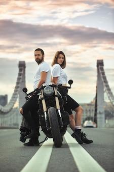 Amore e concetto romantico. bella coppia in moto sta uno di fronte all'altro in mezzo alla strada sul ponte, su doppio solido.