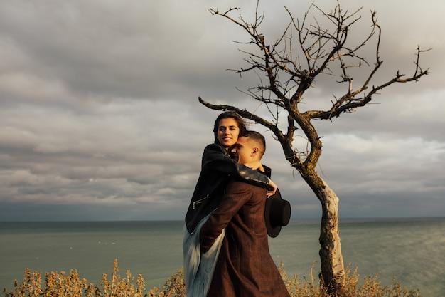 In amore romantico coppia che abbraccia toccando sulla superficie del mare, il sole e le nuvole.