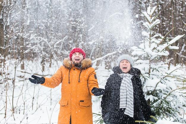 Amore, stagione, amicizia e concetto di persone - felice giovane uomo e donna che si divertono e giocano con la neve nella foresta invernale.