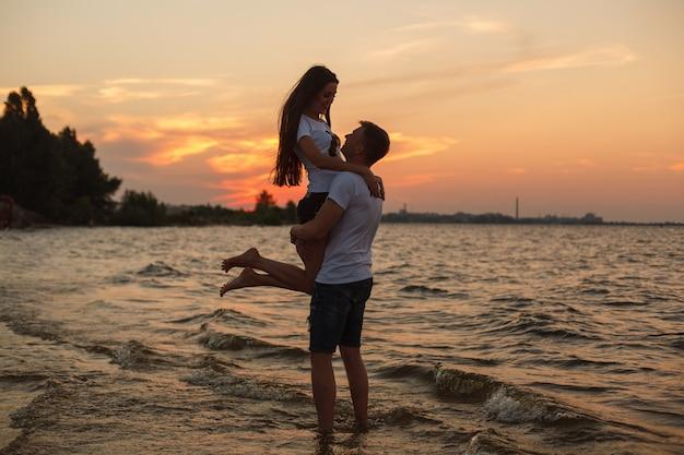 Storia d'amore sulla spiaggia giovane bella coppia amorosa che abbraccia sulla spiaggia al tramonto.