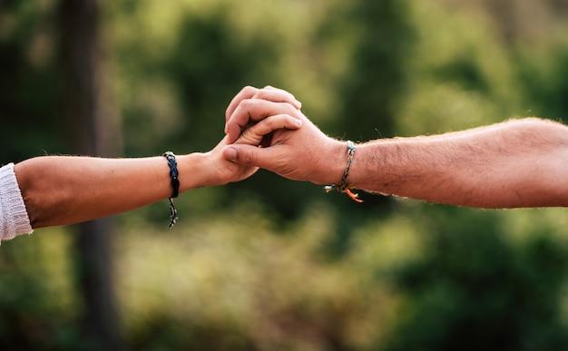 Amore e concetto di squadra con le mani di donna e uomo che si tengono insieme