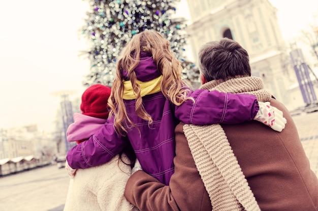 Amali. piccola femmina sveglia che guarda in una direzione con mamma e papà mentre si gode la città invernale
