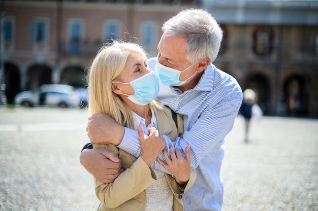 L'amore ai tempi di coronavirus. coppie senior che abbracciano le maschere d'uso all'aperto