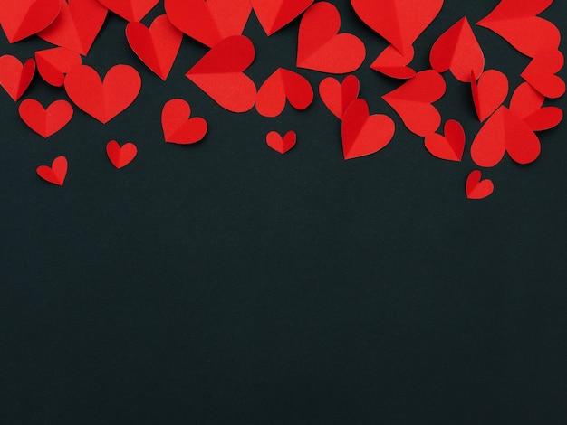 Amore e san valentino con cornice di cuori di carta rossa artigianale su sfondo nero con copyspace.