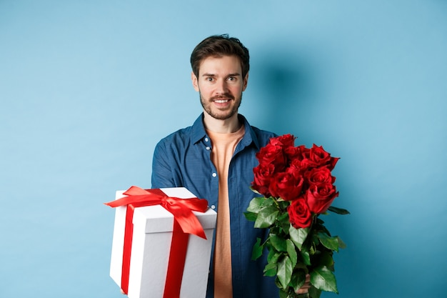 Concetto di amore e san valentino. affascinante giovane uomo dando regalo e bouquet di rose alla ragazza, in piedi su sfondo blu.