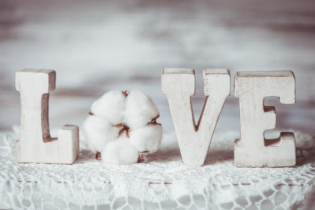 Lettere d'amore in legno sul centrino all'uncinetto, in stile vintage e fiore di cotone