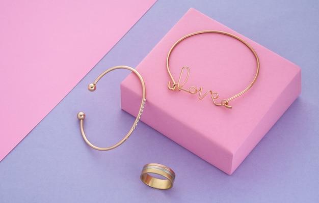 Braccialetto a forma di parola d'amore e bracciale e anello dal design moderno su sfondo rosa e viola con spazio per le copie