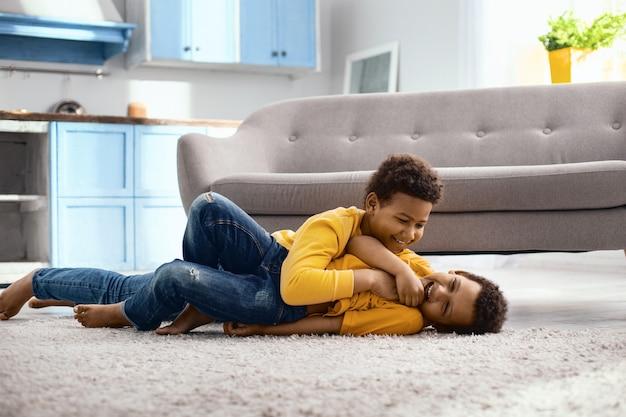 Ti amo. ragazzino sveglio sdraiato sul pavimento e solleticare il suo fratello minore mentre ride forte e felicemente