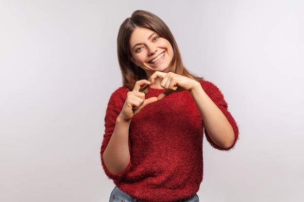 Ti amo ritratto di felice bella ragazza bruna in maglione arruffato a forma di cuore con le mani