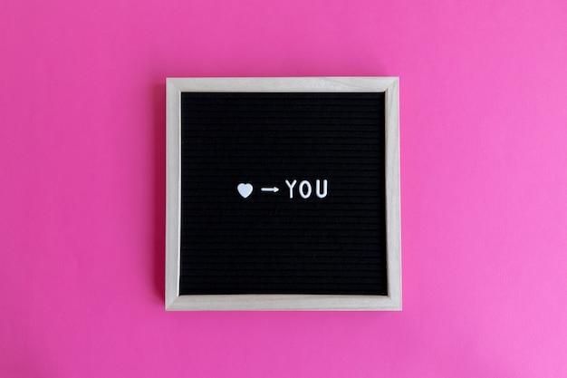 Ti amo citazione su una tavola con cornice in legno su uno sfondo colorato