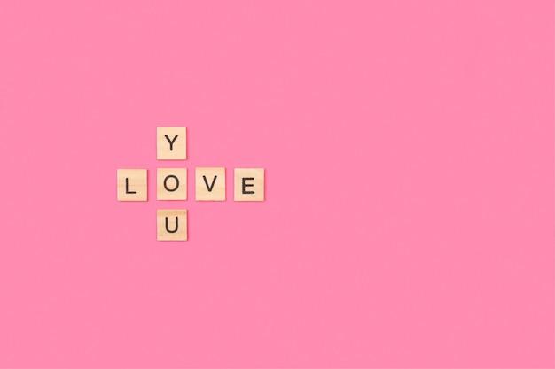 Ti amo scrivere con blocchi di lettere in legno su uno sfondo rosa