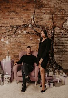 In amore giovane coppia uomo e donna che abbraccia baci vicino a un albero di natale in abiti eleganti.