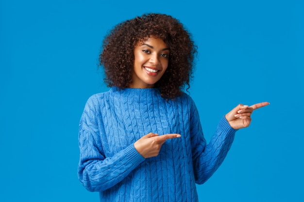 Bella femmina afro-americana adulta con taglio di capelli afro, puntando le dita a destra, suggerendo di andare in direzione, visitare il sito o scaricare l'app, presentare un ottimo prodotto e sorridere soddisfatto, blu