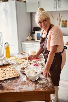 Bella donna anziana in posa nel disordine creativo della sua cucina