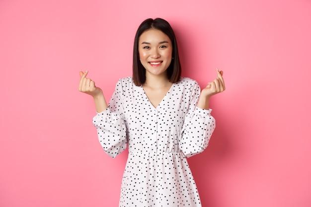 Bella donna asiatica in abito che mostra segni di cuore coreano e sorridente, in piedi su sfondo rosa romantico.