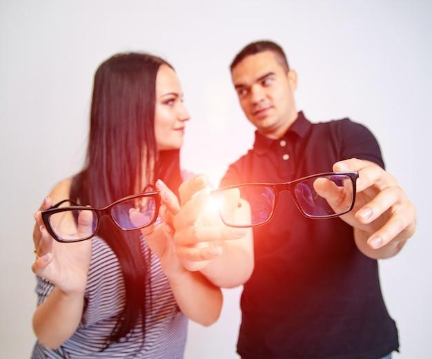Bella coppia attraente che si siedono insieme e si guardano tenere gli occhiali in mano. le giovani coppie che sorridono l'un l'altro mostrano gli occhiali nella cornice nera che si siede su priorità bassa bianca.