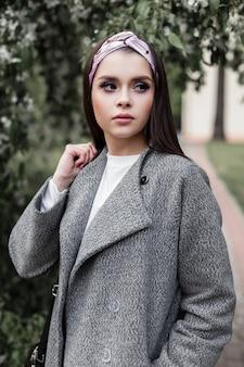 Bella giovane donna adorabile in cappotto alla moda in bandana affascinante alla moda su fondo di fogliame verde all'aperto nel giorno di primavera. moda ragazza in abiti della nuova collezione giovanile pone in strada.