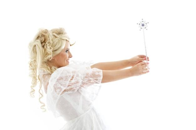 Bella bionda in abito da fata con la bacchetta magica su bianco