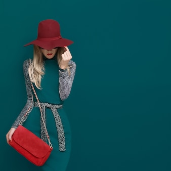 Modello biondo adorabile in cappello rosso alla moda e una frizione rossa sulla parete verde