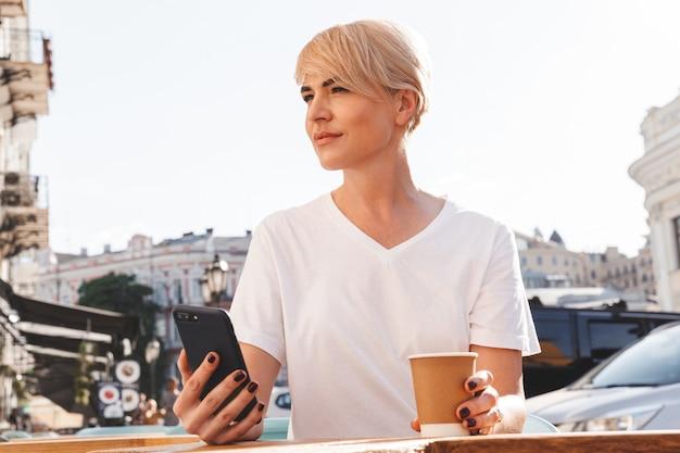 Bella donna bionda che indossa una maglietta bianca utilizzando il telefono cellulare, mentre è seduto in un bar o ristorante esterno in estate e beve caffè dal bicchiere di carta