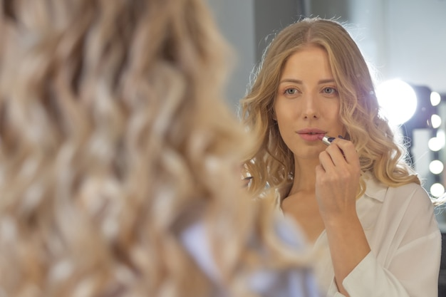 Bella donna bionda con una bella acconciatura che guarda il suo riflesso nello specchio e dipinge le labbra al salone di bellezza