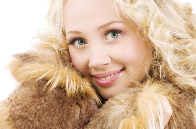Bella donna bionda in pelliccia sul muro bianco
