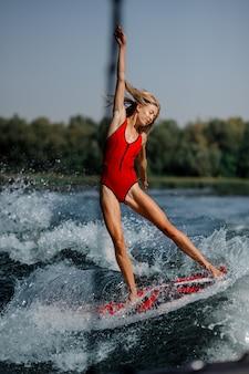 Donna bionda adorabile che pratica il surfing a bordo giù l'acqua blu