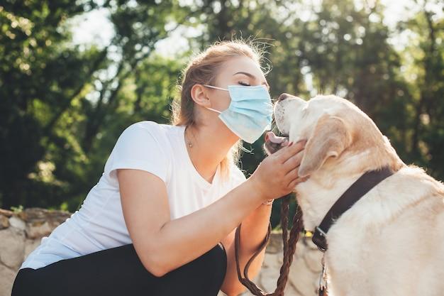 Bella donna bionda con mascherina medica sul viso che gioca con il suo cane fuori durante il blocco