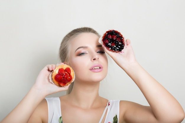 Bella donna bionda con un trucco professionale che tiene dolci cupcakes con bacche vicino al viso