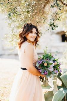 Bella sposa in un lussuoso abito color pastello carino sorridente che tiene un mazzo di fiori nelle sue mani