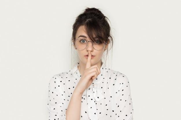 Bella signora castana con gli occhiali che gesturing il segno di silenzio su una parete bianca che guarda direttamente