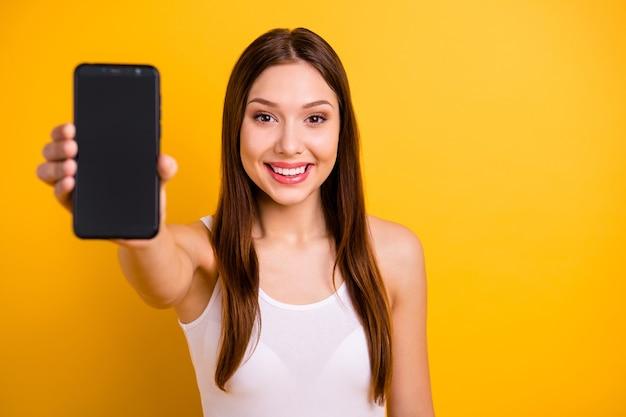Bella donna castana con labbra rosse in posa contro il muro giallo
