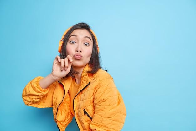 Bella bruna giovane donna asiatica mantiene le labbra arrotondate ha un'espressione romantica attende per il bacio si diverte ad ascoltare musica tramite le cuffie indossa una giacca arancione posa contro il muro blu