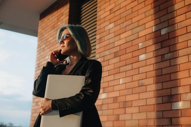 Bella donna d'affari con i capelli blu sta discutendo al telefono mentre posa su un muro di pietra che tiene il suo computer