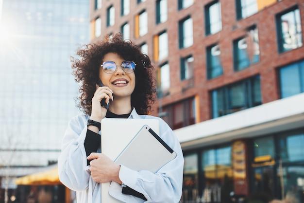 Bella uomo d'affari caucasico con i capelli ricci sta parlando al telefono mentre posa con alcuni dispositivi moderni