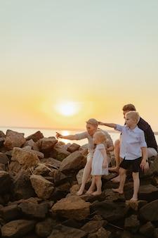 Bella famiglia caucasica con bambini bambino godersi il tramonto sulla spiaggia?