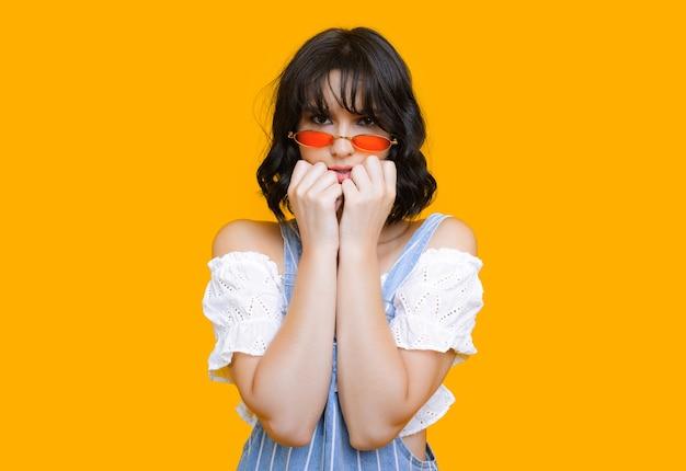 Bella ragazza caucasica sta toccando il viso mentre guarda attraverso gli occhiali e posa su un muro giallo con spazio libero