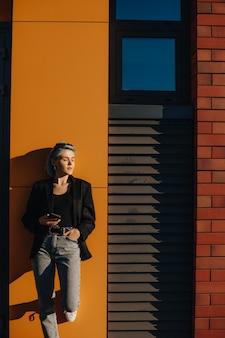 Bella ragazza caucasica con capelli blu in posa su una parete gialla fuori con gli occhiali da vista e in possesso di un telefono