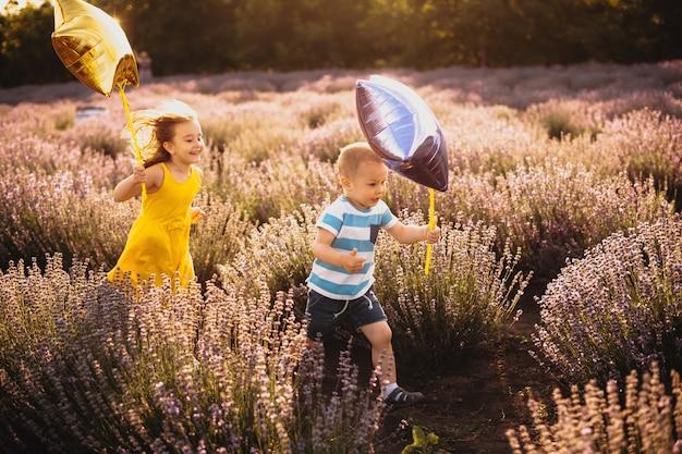 Adorabili bambini caucasici che corrono contro il sole con alcuni palloncini attraverso un campo di lavanda