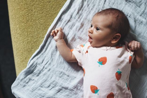Bella ragazza neonata caucasica sta guardando i suoi genitori con la bocca aperta sdraiato su una trapunta