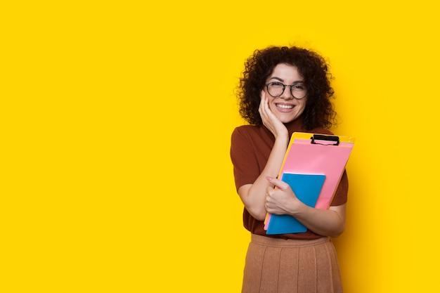 Bella studentessa caucasica con capelli ricci e occhiali da vista è in posa mentre tiene alcuni libri