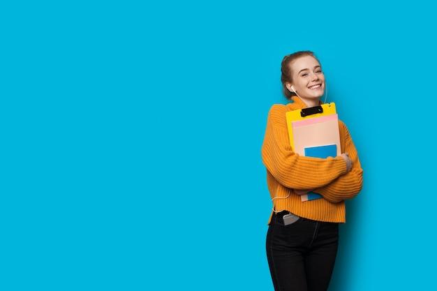 Bella studentessa caucasica con capelli rossi e lentiggini è in posa con auricolari e alcuni libri su una parete blu con spazio libero