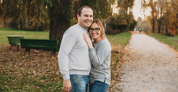 Bella donna caucasica guardando attraverso gli occhiali mentre sorride e abbraccia il marito durante una passeggiata nel parco
