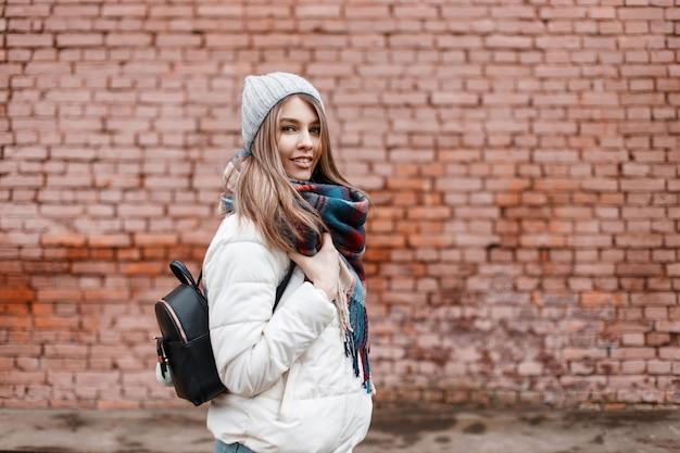 Bella allegra giovane donna positiva con un bel sorriso in una giacca bianca elegante con una calda sciarpa di lana e con uno zaino alla moda nero è in piedi vicino a un muro di mattoni vintage. bella ragazza