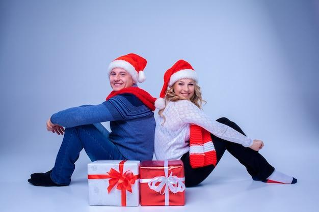 Bella coppia di natale seduta con regali